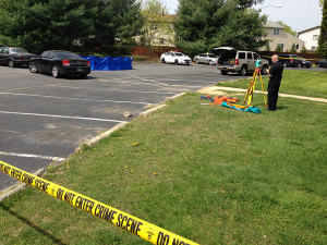 Blue tarp covered body of homicide victim in parking lot at Pine Grove Apartments in Dover.