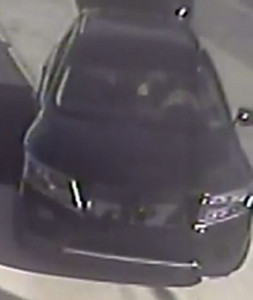 Police released surveillance image of SUV with broken grill fleeing scene of gas station robbery and shooting.