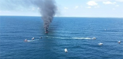 Smoke pours from 46-foot sailboat that caught fire off Ocean City, New Jersey. (Photo courtesy Coast Guard)