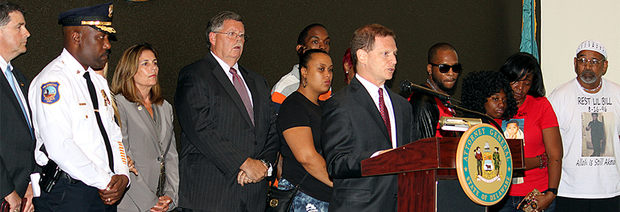 Attorney General Matt Denn announces indictments against members of a Wilmington street gang, while surrounded by law enforcement, Department of Justice prosecutors, and family members of murder victims. (Photo: Delaware Department of Justice)