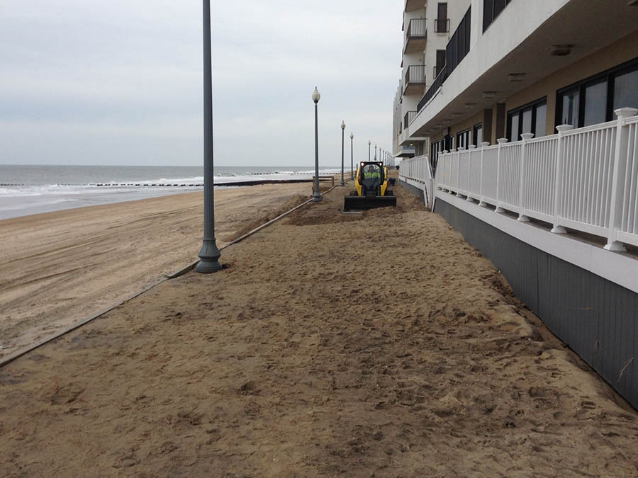 A workers uses a small bulldozer to clear sand from the boardwalk at the Henlopen Hotel in Rehoboth Beach. (Photo: Delaware Free News)