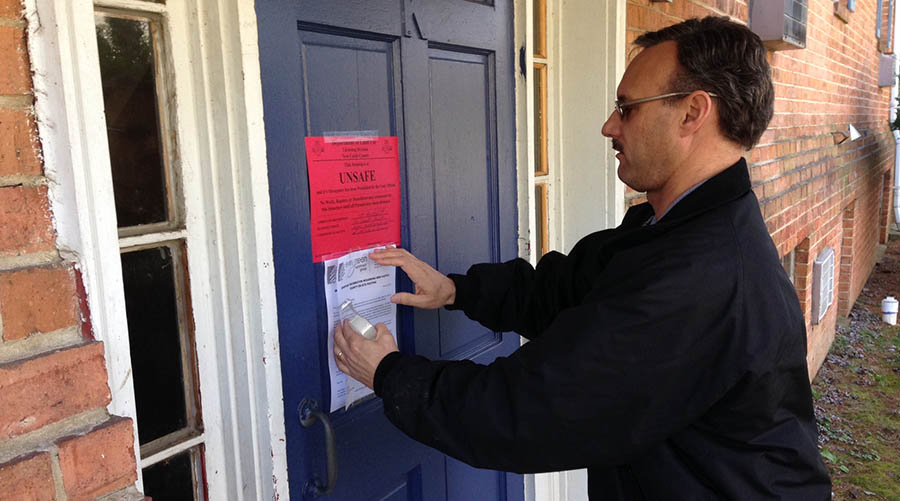 New Castle County emergency official Dave Carpenter posts notice of unsafe conditions on building at Hidden Valley complex. (Photo: Delaware Free News)