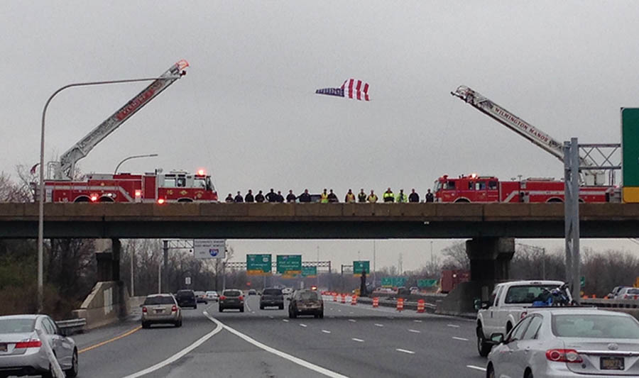 Wind whipped flag held high by firetrucks on Route 141 overpass as funeral procession for Officer Jacai D. Colson passed by below on Interstate 95. (Photo: Delaware Free News)