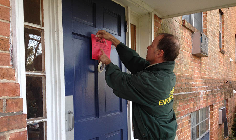 Code enforcement officer Frank Walsh posts condemnation order on door of building at The Evergreen Apartments at Riverfront Heights. (Photo: Delaware Free News)