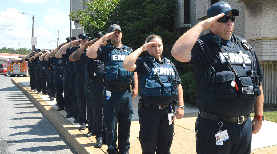 Emergency medical services members salute as body of Tim McClanahan arrives at medical examiner's office. (Photo: Delaware Free News)