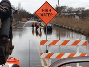 Firefighters escort women to safety after their cars became stranded in flooding from Nonesuch Creek on Airport Road. (Photo: Delaware Free News)